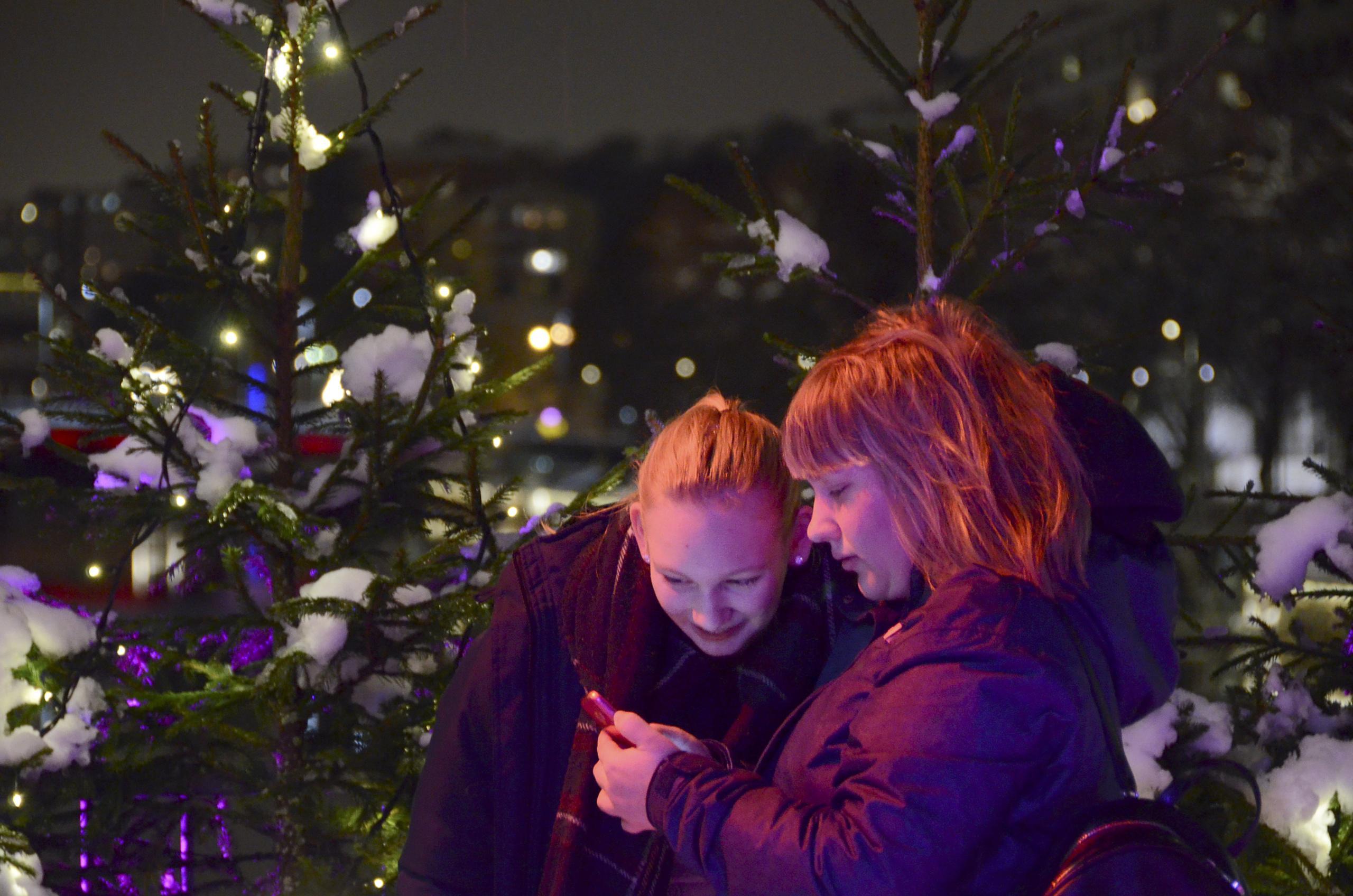 Teatterisilta talvivalaistuksessa, nuoret henkilöt tutkivat puhelintaan.