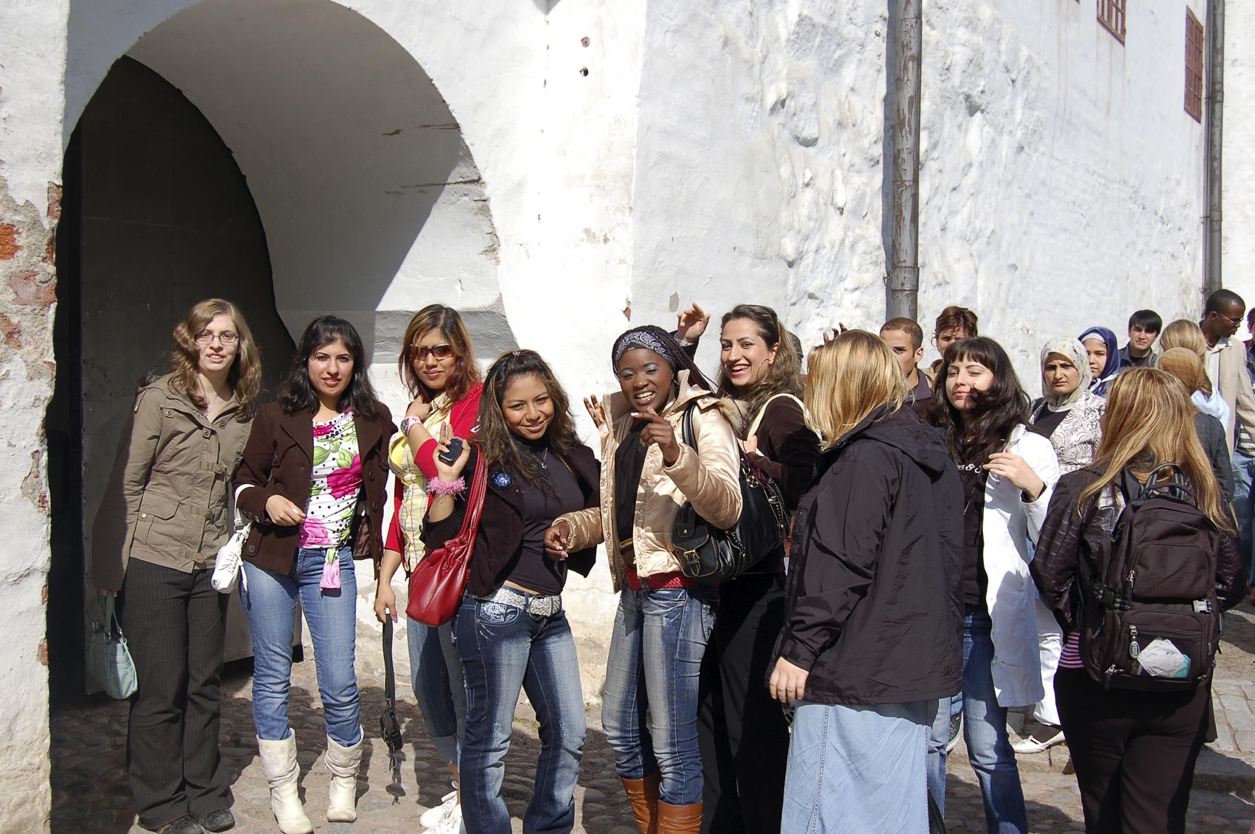 Turun linnan sisäänkäynti, jonka edessä poseeraa kansainvälinen nuorisoryhmä.