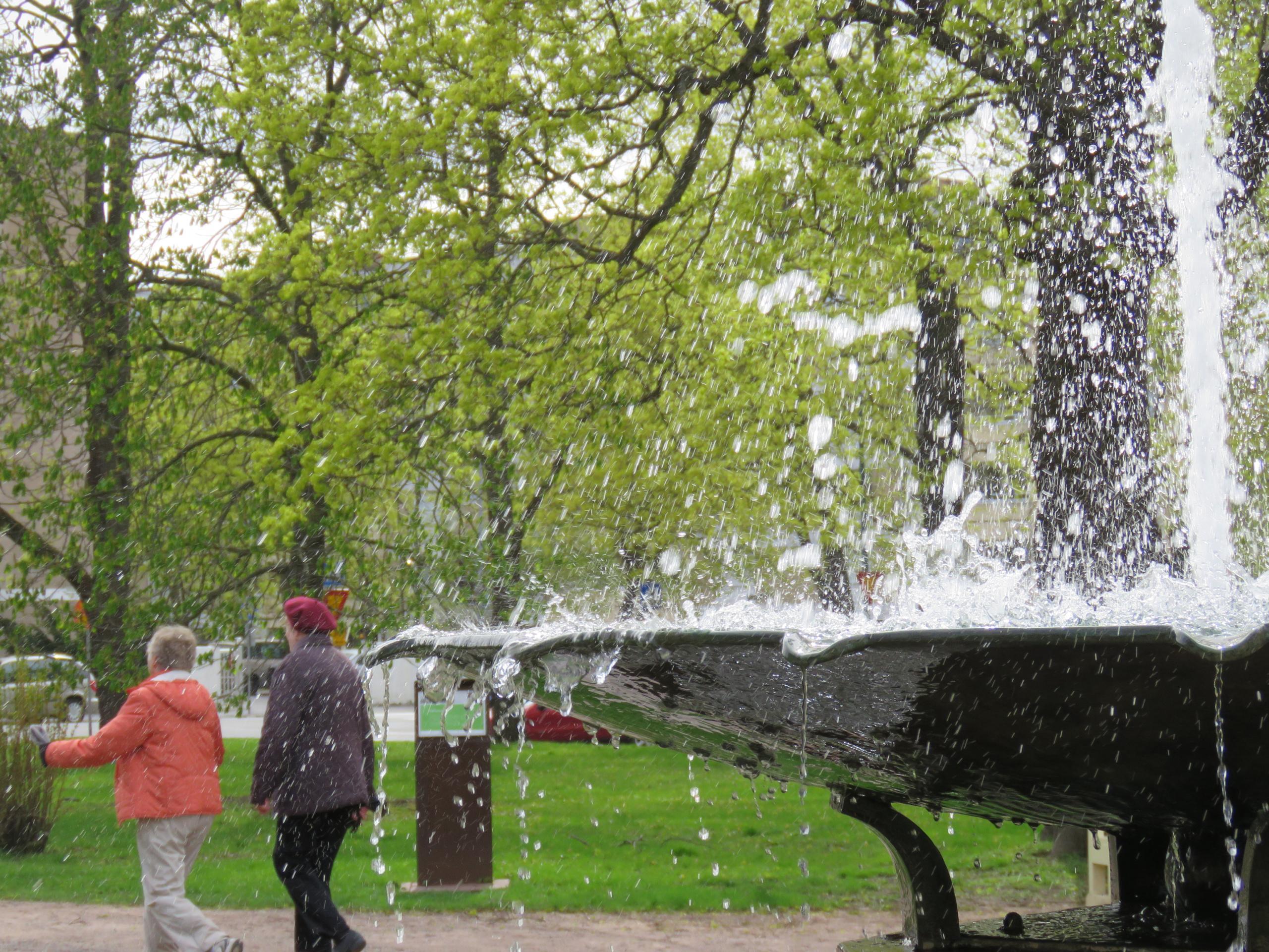 Etualalla pulppuava maljan muotoinen iso suihkulähde, taustalla ihmisiä ja vehreää puistoa.