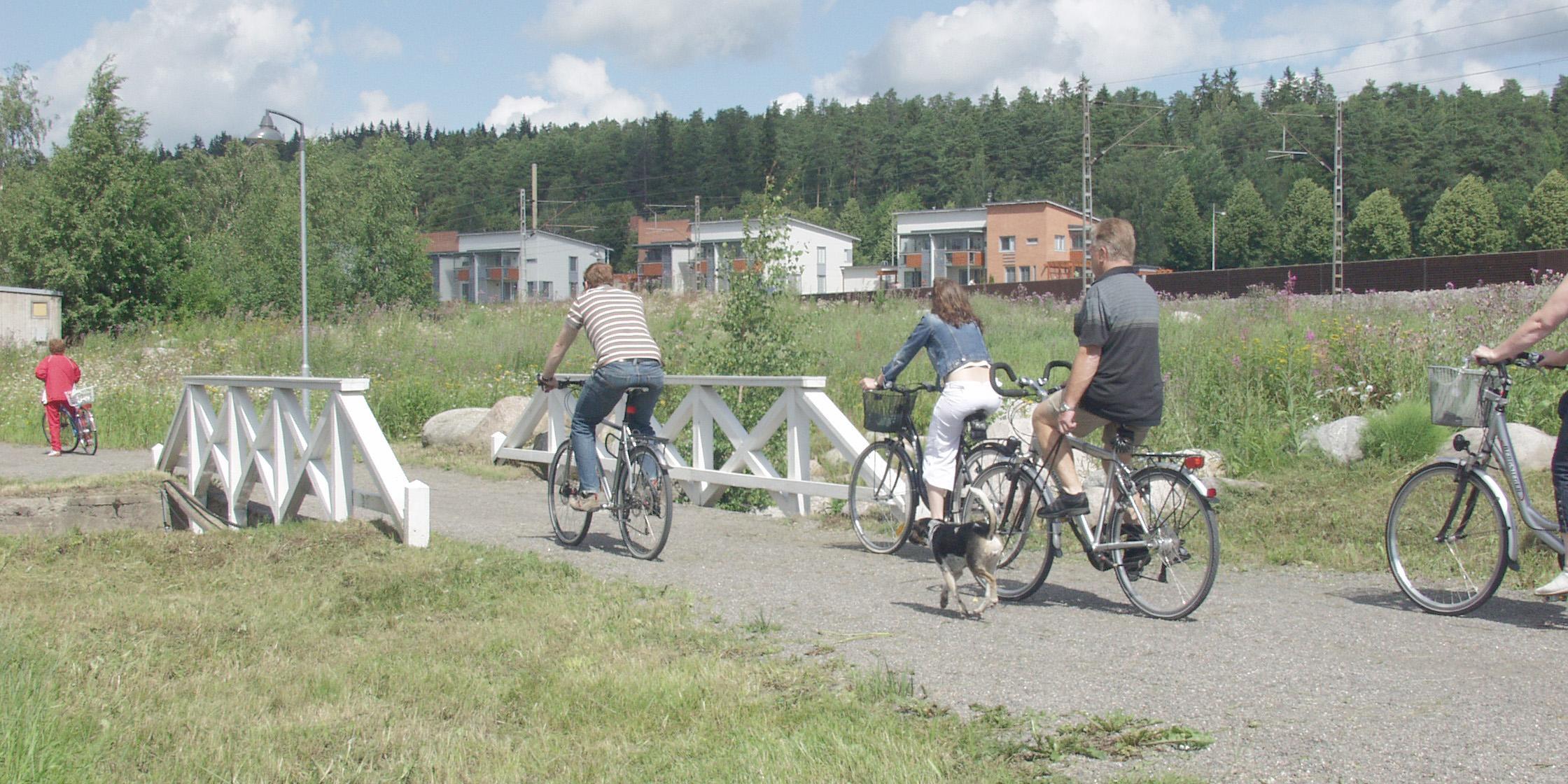 Pyöräilijöitä vihreässä lähiluontoympäristössä, rakennetulla reitillä. Yhdellä pyöräilijällä myös koira mukana.