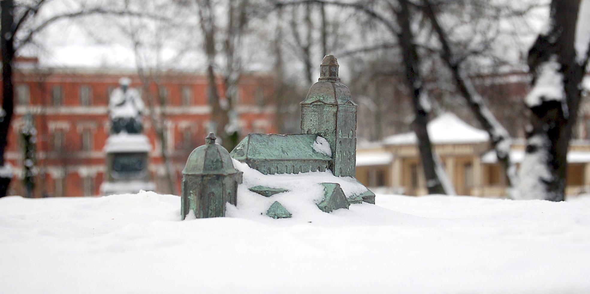 Pieni pronssinen veistos kirkkorakennuksesta puistossa, talvinen kuva.