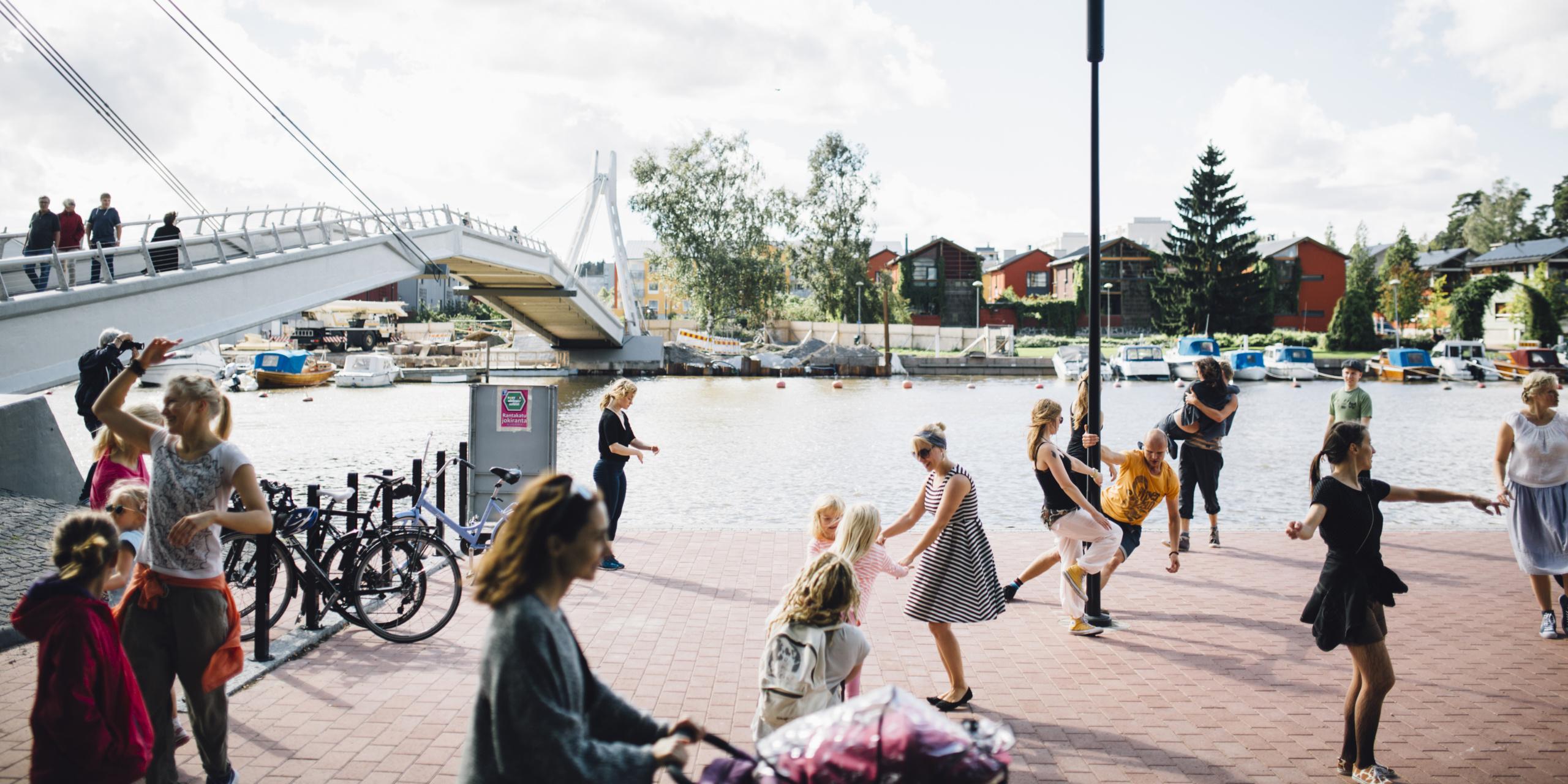 Kaupungin rantanäkymässä tanssivia ihmisiä, lapsia ja aikuisia. Taustalla veneitä ja rakennuksia.