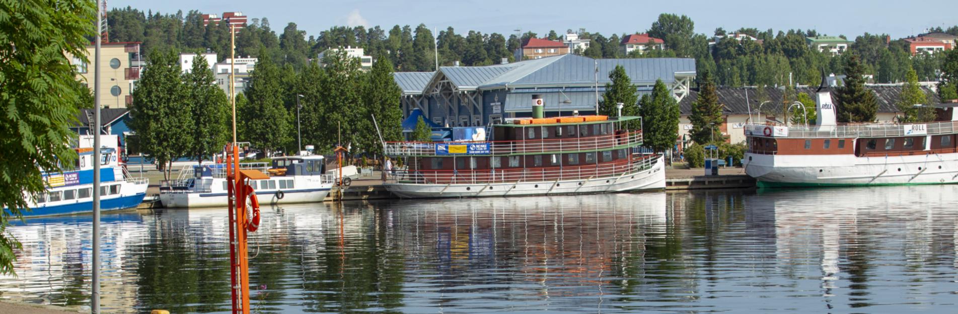 Kuopion Kuopion Satama: Valkokylkisiä laivoja ja sinisiä satamarakennuksia. Kuvaaja: Vicente Serra.