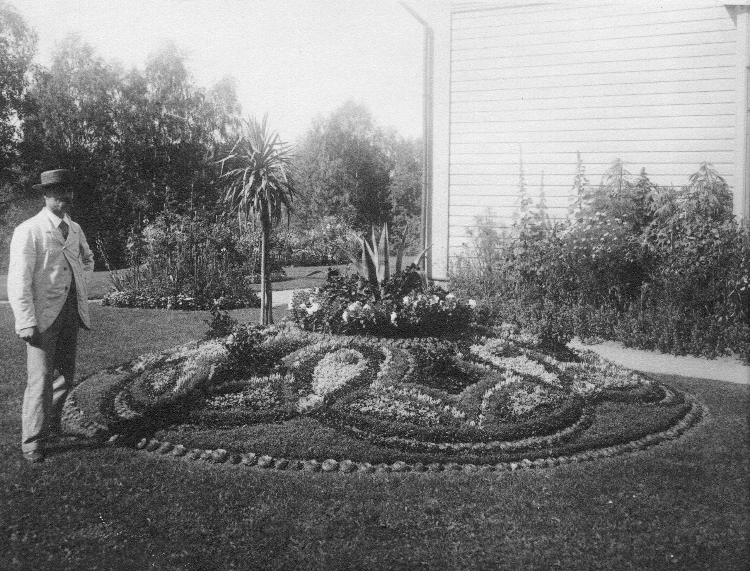 Mustavalkoinen vanha kuva, jossa hattupäinen herra seisoo näyttävän ja koristeellisen kesäkukkatapettiryhmän vieressä. Taustalla hoidettua pihapiiriä ja perennaistutuksia.