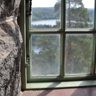 Näköala Aulangon näkötornin paksuihin harmaakivisiin seiniin upotetun vanhan ikkunan läpi kohti Aulangonjärven kansallismaisemaa.