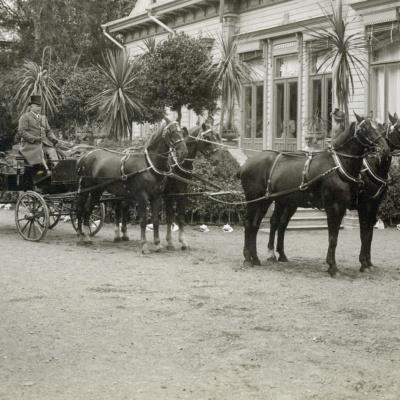 Mustavalkoinen historiallinen kuva Karlbergin kartanon (nykyään Aulanko) hoidetulta pihalta. Etualalla neljän hevosen valjakko kiesien edessä ajurin ja apumiehen kanssa. Taustalla Karlbergin kartanon puisia rakennuksia.