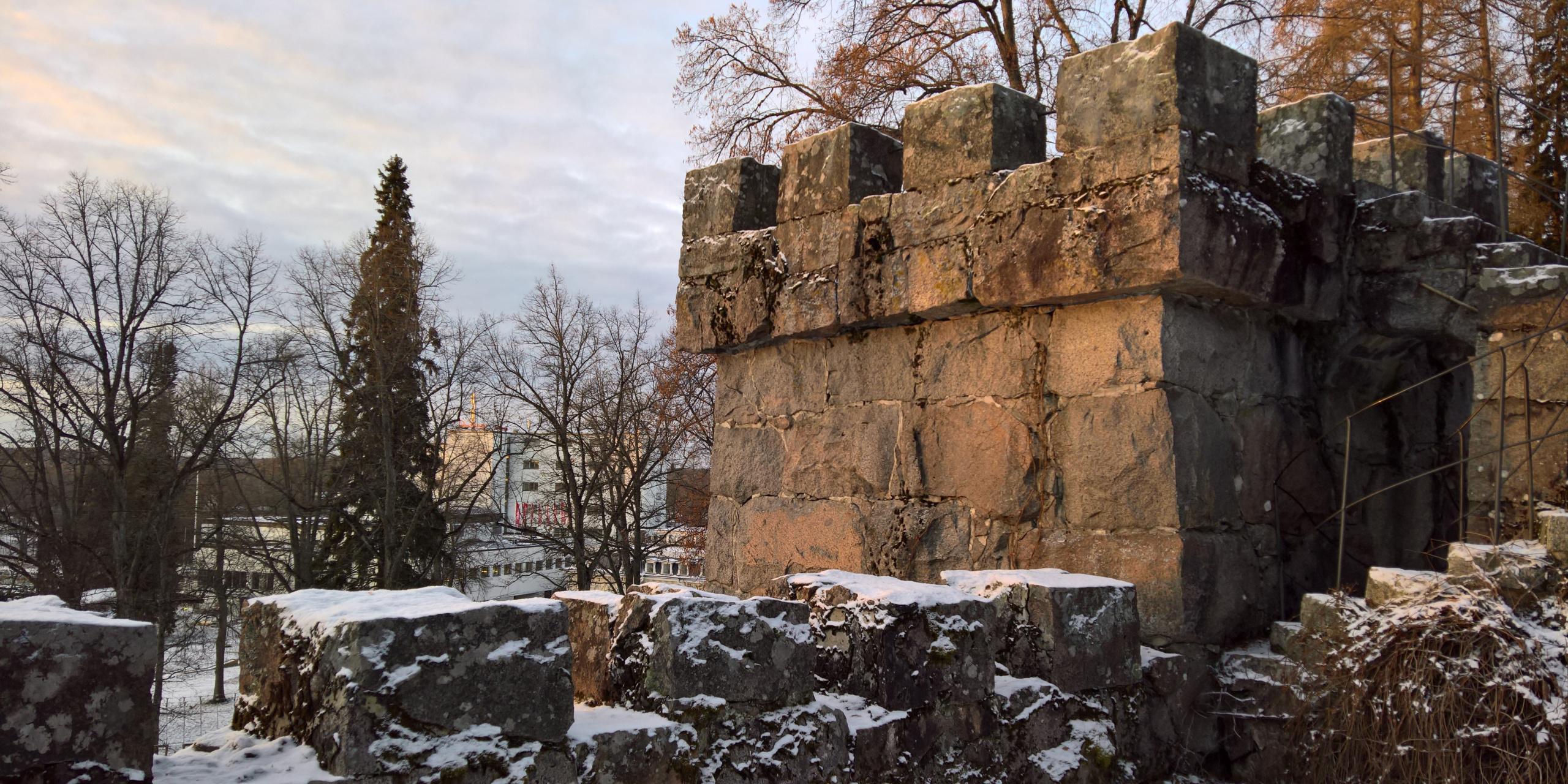 Talvinen kuva vähän punertavassa ilta-auringossa, hiukan lunta maassa. Etualalla Aulangon vanhan graniittilinnan jyhkeä harmaakivinen torni ja taustalla kauempana puiden oksien takana siintää Aulangon valkoiset hotellirakennukset.