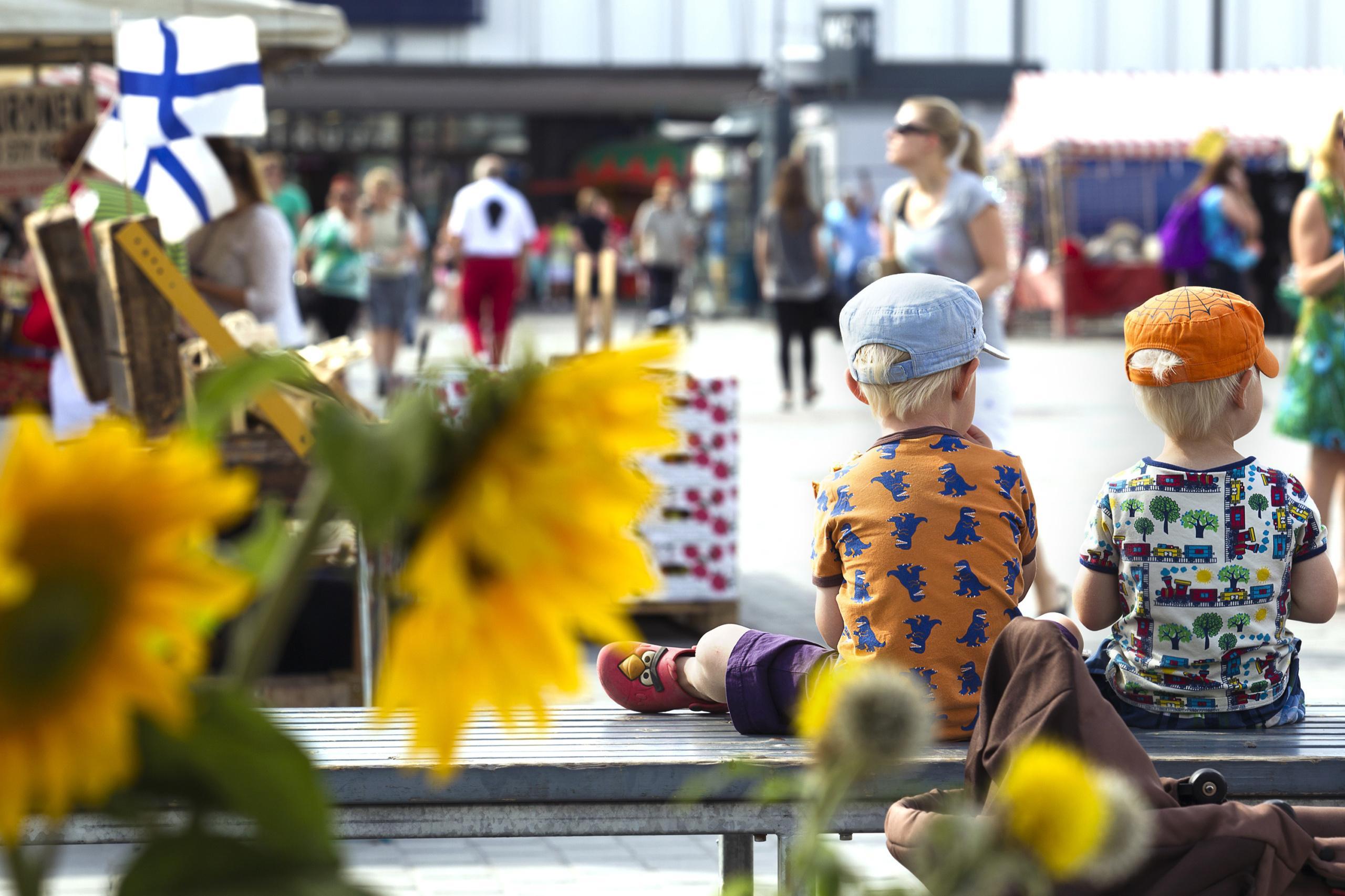 Kaksi lippalakkipäistä pikkupoikaa istuu aurinkoisen päivänä penkillä, selin kuvaajaan, kuvan oikeassa reunassa. Taustalla epätarkkana torin ihmisvilinää ja etualalla vasemmalla lähellä auringonkukkia.