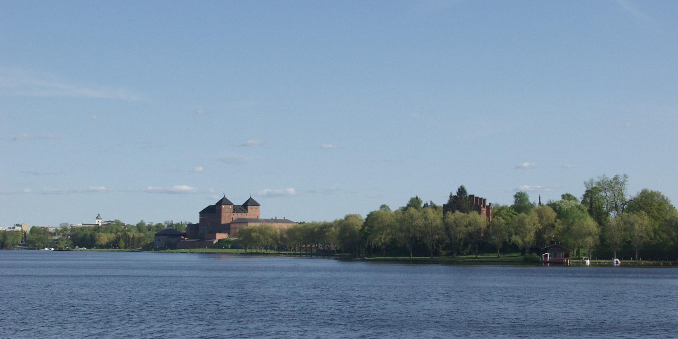 Kesäinen rantasiluetti Vanajaveden yli, jossa näkyy hämeen keskiaikainen linna ja sen lähiympäristöä sekä kaupungin keskustan rakennuksista kohoava kirkon torni.
