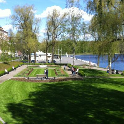 Näkymä keväiseen Laivarannanpuistoon korkeammalta, Viipurintien sillalta. Puut vihertää hennosti ja puiston nurmikko on juuri ajettu. Puistossa on ihmisiä istuskelemasa ja kävelemässä. Puiston takana näkyy puiden välistä valkoinen Rantacarinon rakennus ja rantalaituri.