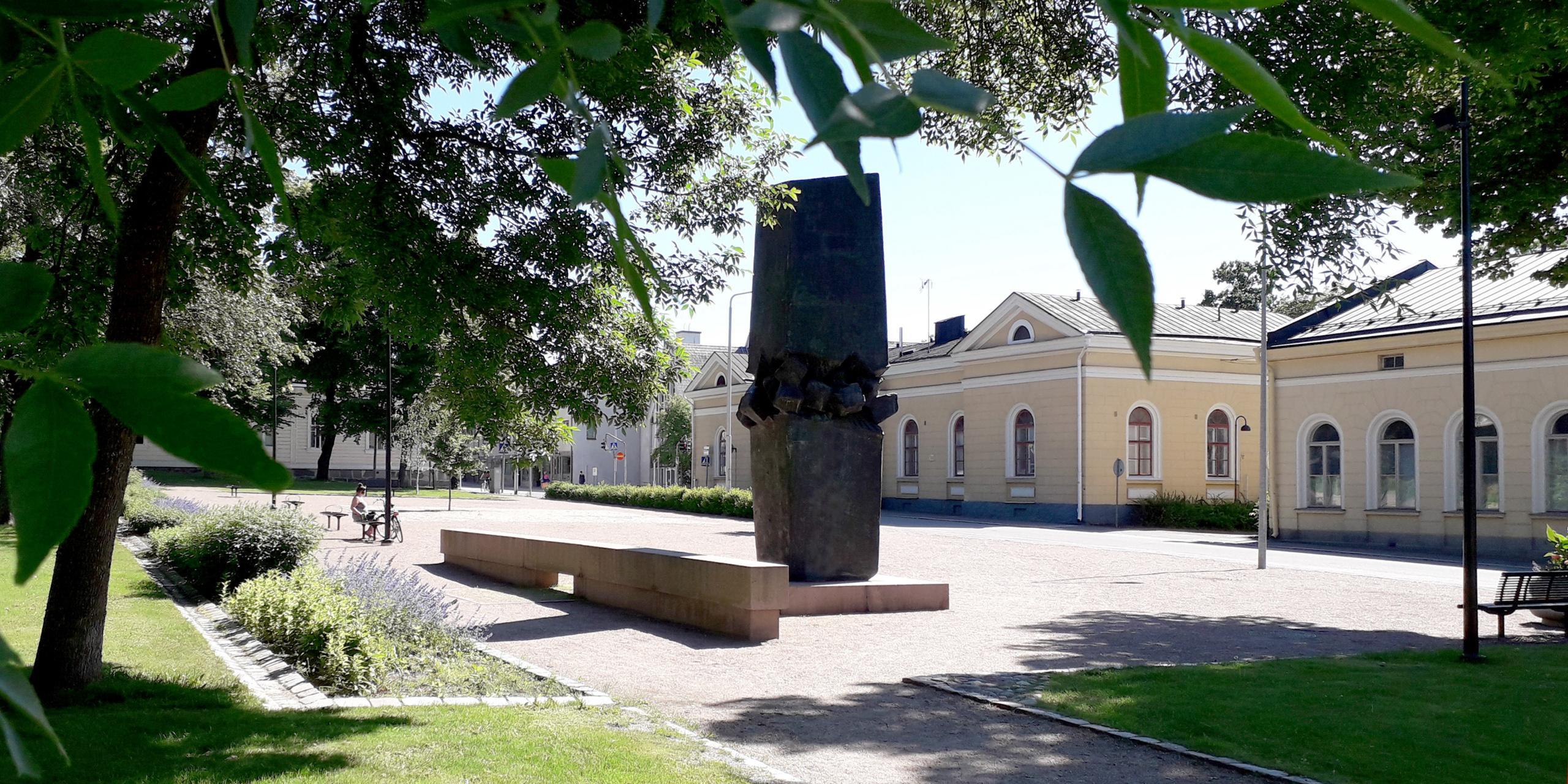 Aurinkoinen aukio kuvattuna puiden lehvästön yläreunasta rajaamana, aukiolla isokokoinen tumma pronssiveistos, jossa kaksi 'lohkaretta' päälekäin ja niiden välissä pienempi 'louhikko'. Jalusta ja pitkä, veistoksesta irrallinen muuri on punaista graniittia. Puistossa kukkaistutuksia ja penkkejä, penkillä istuskelee henkilö. Taustalla vaalean okran värisiä vanhoja kivirakennuksia valkopuitteisine kaari-ikkunoineen.