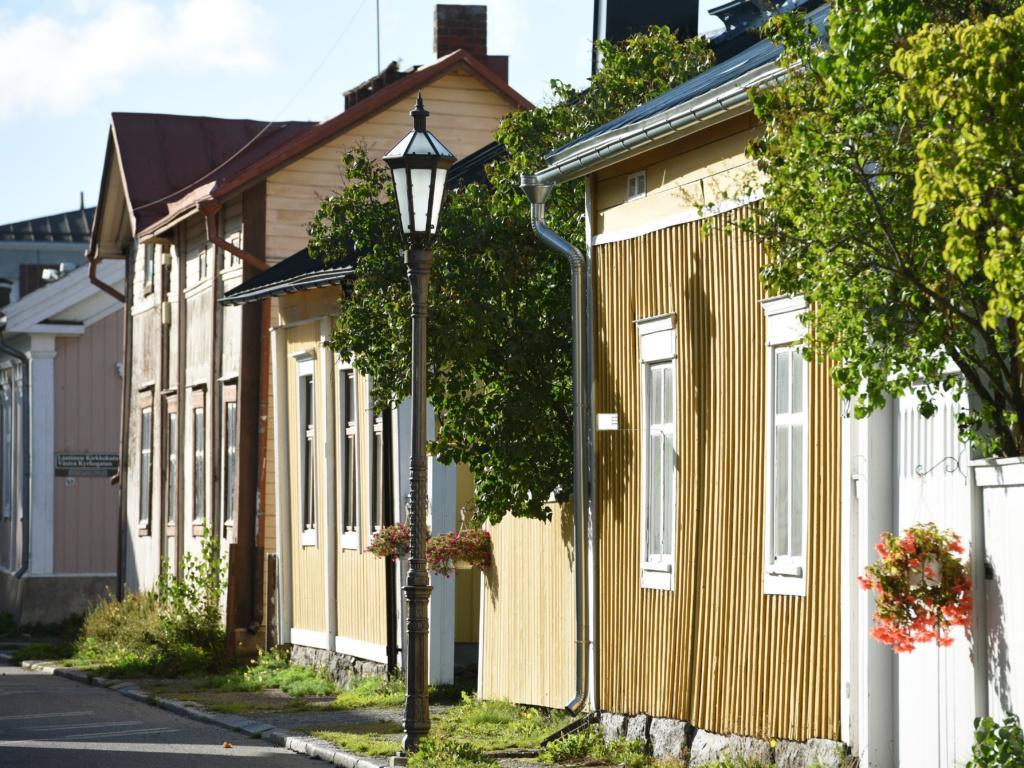 Kadun varressa lähikuvassa vanhoja puutaloja, Ruskean ja okran värisiä, osassa valkoiset ikkunapuitteet. Julkisivuista ja niitä jatkavista aidoista muodostuu umpikortteli, aitojen päälle talojen välistä pilkottaa puita. Kapea ruohottunut jalkakäytävällä, jossa vanha lyhtymallinen ja koristeellinen valaisintolppa. Kesäkukkiaroikkuu amppeleissa.