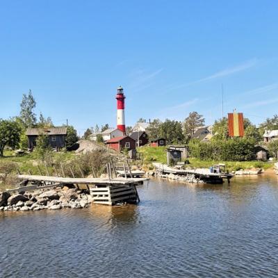 Vanha kalastajakylä kesällä, rantaviivassa kiviröykkiöille perustettuja vähän vinksottavia puulaitureita, taustalla rakennuksia ja keskellä kuvaa puna-valkoinen majakka.
