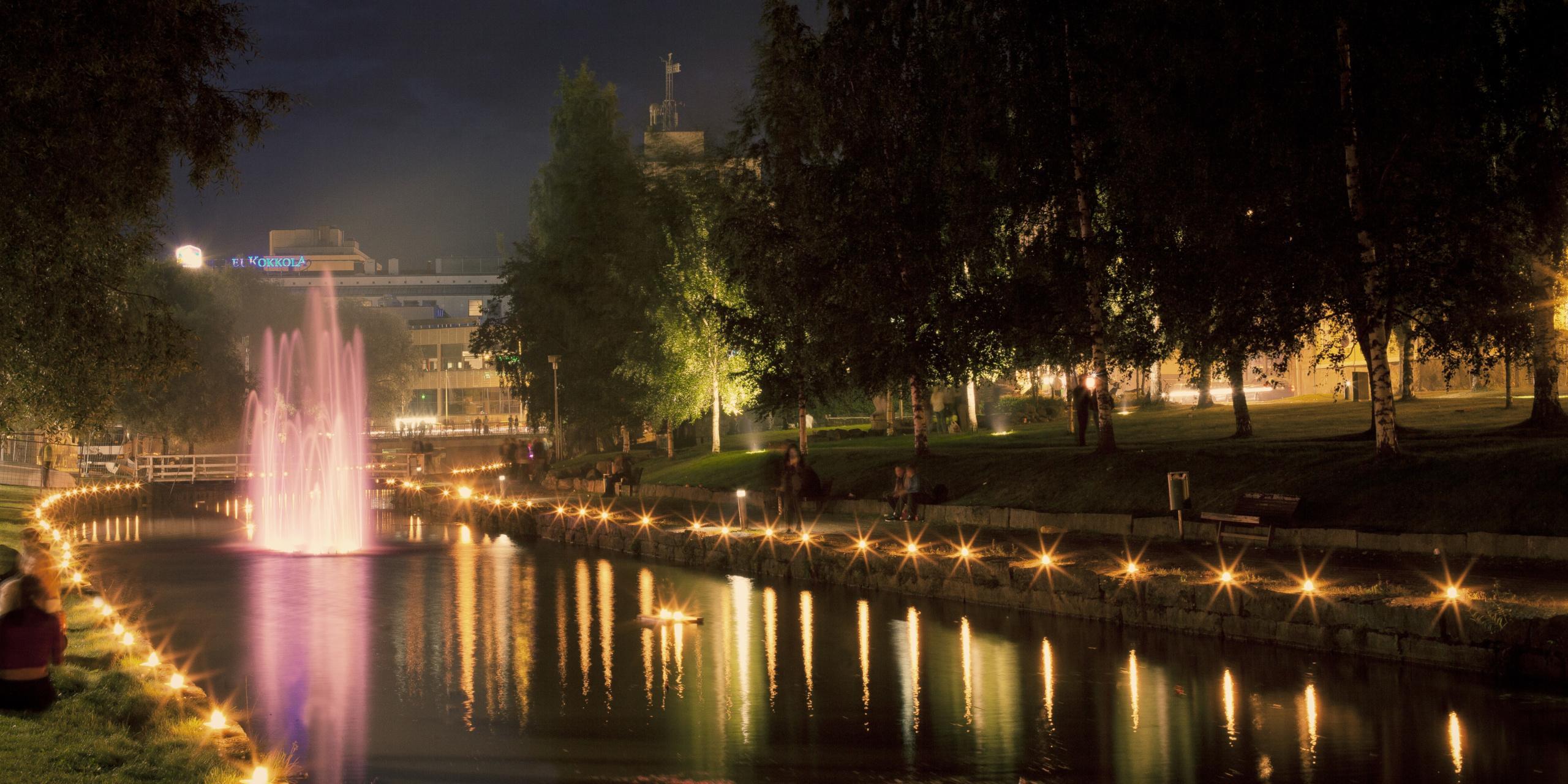 Iltakuva kanaalista ja sen korkeasta värikkäästi valaistusta suihlkulähteestä. Kanaalin reunoille aseteltu tiheät valorivistöt, ehkä kynttilät ja taustan puiston puita on valaistu alhaaltapäin. Puistossa on ihmisiä ja kuvan taustalla kaupungin rakennuksia.